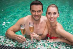 Happy couple celebrating in pool. Waist up portrait of smiling man and woman standing in water. They are holding glasses of champagne solemnizing anniversary in Stock Photos