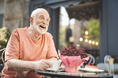 Joyful old man laughing in delight outside. Waist up portrait of smiling mature male sitting at table with cup of tea. He is looking forward with amazement and Royalty Free Stock Image