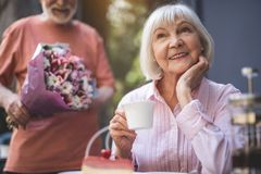 Delighted elderly female waiting for spouse in cafe. Waist up portrait of smiling senior lady sitting at table and drinking tea. She is touching face in Stock Photos