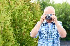 Happy Senior Tourist Taking Pictures in Park. Waist up portrait of smiling senior man taking pictures in park using vintage photo camera while travelling Royalty Free Stock Image
