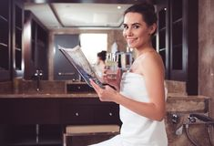 Attractive happy girl sitting with journal in bathroom. Waist up portrait of smiling woman reading magazine after taking bath. She is wrapped in white towel stock image