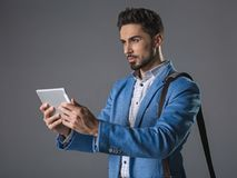 Concentrate bearded man using tablet. Waist up portrait of thinking businessman with shoulder bag surfing internet on clipboard. Isolated on gray background Stock Photos