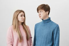 Waist up portrait of young female and male wearing knitted colourful sweaters having discontent looks pouting cheeks Royalty Free Stock Photography