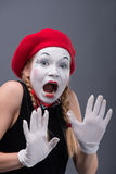 Waist-up portrait of young mime girl showing Stock Photo