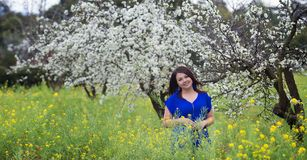 Waist up portrait of young woman in bright blue top in blossoming orchard and yellow mustard field, smiling, looking straight to t Stock Image