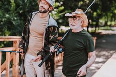 Waist up of a positive elderly angler with his son. Waist up of a cheerful aged men holding fishing equipment while spending time with his son royalty free stock photos