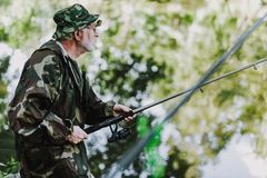Waist up of a retired angler fishing on the weekend. Waist up of a professional fisherman angling while holding a rod stock photography
