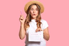 Waist up shot of amazed beautiful woman holds pen and menstrual calendar, shows five day marked with hearts, isolated over pink stock photo
