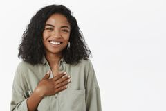 Waist-up shot of amused attractive and stylish young african american female with curly haircut being pleased receiving. Thanks being grateful for nice words stock image