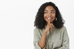 Waist-up shot of amused excited good-looking artistic african american woman with curly hairstyle smiling joyfully. Having idea gazing left and asking keep royalty free stock photos