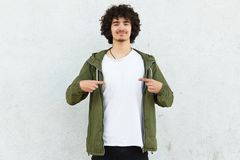 Waist up shot of attractive guy with curly hair, wears green anorak, points at blank t shirt, shows free space for your logo, mode. Ls over white concrete wall royalty free stock photos