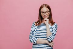 Waist up shot of attractive young woman holds chin, keeps hands partly crossed, being deep in thoughts, stands against pink. Background with copy space for your royalty free stock images