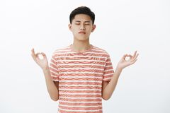 Waist-up shot of calm focused attractive asian male student taking control of thoughts, standing in lotus pose with zen royalty free stock images