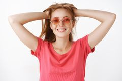 Waist-up shot of carefree energized and cute ginger woman with freckles and cute broad smile holding hair behind with stock image
