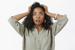 Waist-up shot of concerned girl in stupor. Portrait of shocked african american businesswoman standing anxious and. Shocked opening mouth holding hands on head royalty free stock images