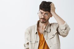 Waist-up shot of confused good-looking young man with beard and dark stylish hairstyle scratching head and frowning with royalty free stock photos