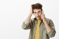 Waist-up shot of cute friendly-looking mature male coworker with blue eyes and bristle, talking on smartphone. Scratching hair while gazing at camera with cute Royalty Free Stock Images