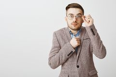 Waist-up shot of cute shy and insecure male nerd in glasses and fancy jacket holding fist near body popping eyes. Touching rim of eyewear standing unconfident stock photos