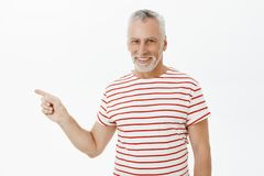 Waist-up shot of delighted carefree charismatic happy old man with grey beard in striped t-shirt smiling satisfied and. Confident pointing left showing perfect stock photos