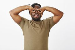 Waist-up shot of funny carefree african-american guy in olive t-shirt, holding hands over eyes and making faces. Mimicking goggles or eyewear while fooling stock photos