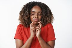 Waist-up shot of funny and emotive hopeful african-american woman eager to get new car cross fingers for good luck and. Dream come true close eyes and praying stock photos