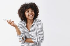 Waist-up shot of happy and carefree modern African American businesswoman in trendy striped blouse holding glasses in. Hand and gazing at upper right corner royalty free stock image