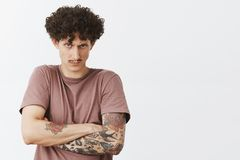 Waist-up shot of intense angry and young curly-haired man with moustache and tattoos holding offence inside. Frowning looking from under forehead with scorn stock photography