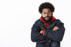 Waist-up shot of intense and bothered gloomy angry african american bearded man in glasses looking with judgement and. Disapproval frowning and sulking crossing royalty free stock photo