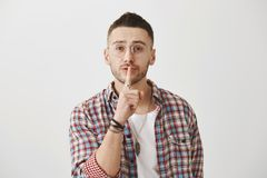 Waist-up shot of kind friendly man in glasses, saying shush with slight smile, holding index finger over mouth, asking. To keep secret or remain silent over Stock Image