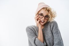 Waist-up shot of modern stylish good-looking european female with blond hairstyle in glasses warm winter beanie and. Sweater biting finger flirty and cheeky royalty free stock photo