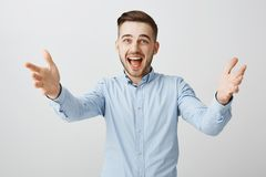 Waist-up shot of pleased excited good-looking adult handsome guy with bristle in formal blue shirt pulling hands towards stock photography