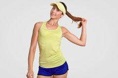 Waist up shot of self confident beautiful healthy tennis player holds pony tail, dressed in sportswear, poses against white studio stock photos