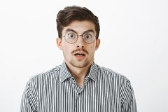 Waist-up shot of shocked surprised funny bearded guy with moustache in round transparent eyewear, dropping jaw, saying. Wow and staring at camera, seeing Royalty Free Stock Photo