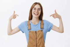 Waist-up shot of smart self-assured european woman in glasses and overalls pointing at herself with proud confident. Joyful smile standing pleased against gray stock photography
