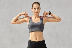 Waist up shot of sporty woman keeps both hands on shoulders, does exercises during morning workout, wears casual top and leggings,. Looks directly seriously at royalty free stock image