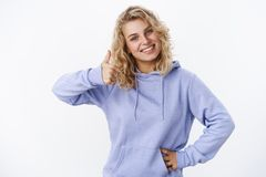 Waist-up shot of supportive pleasant and satisfied attractive european fair-haired female in hoodie tilting head. Joyfully showing thumb up in like and approval royalty free stock photo