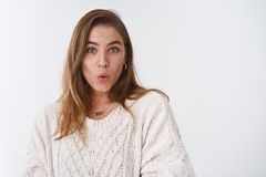 Waist-up shot surprised amused impressed attractive Caucasian female model wearing loose sweater folding lips saying wow. Astonished widen eyes intrigued stock photo
