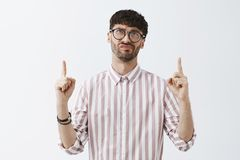 Waist-up shot of upset disappointed and snobbish good-looking guy in glasses and striped shirt pointing and looking up. Frowning and smirking from dislike being royalty free stock photos
