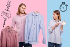 Waist up of slow thinking man and his impatient girlfriend. Hard decision. Waist up of young handsome men holding shirts and choosing the best one while his Royalty Free Stock Image