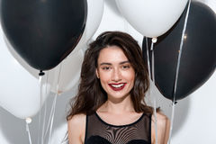 Waist up of a smiling model with balloons stock image