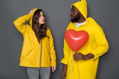 Waist up of stressed young couple wearing yellow raincoats against gray background stock images