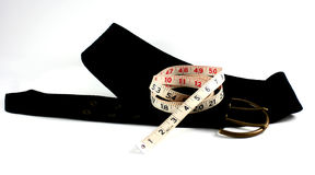 Waist Watchers. Symbols of an apparent diet, a measuring tape and a goal-size belt join together as incentive reminders Royalty Free Stock Photo