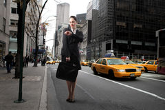 Wait for a bus. Businesswoman standing on a street and looking at her watch Stock Photography