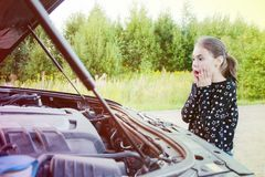 Wait for help on the road. Portrait of a surprised girl standing next to a car and an open hood royalty free stock photos