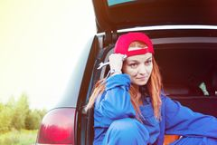 Wait for help on the road. Portrait of a young sad woman sitting in her car in working uniform with a wrench stock image