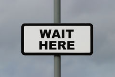 Wait Here. Sign, Wait Here Stock Images