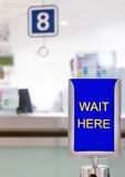 WAIT HERE before counter. Sign with text WAIT HERE before counter Stock Image