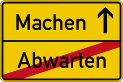 Wait and make. The German words for wait and make (abwarten and machen) on a road sign Stock Photos