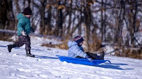 Wait for Me. Little boy runs after another boy headed downhill in toboggan Royalty Free Stock Photo