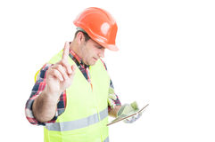 Wait a minute concept with constructor holding tablet Stock Images
